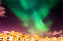 Aurora borealis groene sterrige nacht over de stad en de huizen stock afbeeldingen