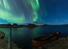 Aurora borealis in Iceland above a lake with boat Stock Photo
