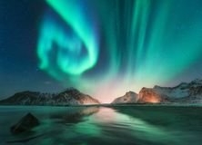 Aurora borealis in Lofoten islands, Norway. Aurora. Green northern lights. Starry sky with polar lights. Night winter landscape with aurora, sea with sky stock image