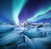 Aurora Borealis, Lofoten islands, Norway. Nothen light, mountains and frozen ocean. Winter landscape at the night time.