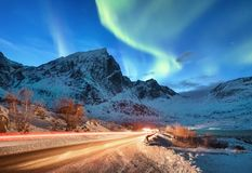 Aurora borealis on the Lofoten islands, Norway. Road traffic and blur car light. Green northern lights above mountains. Night sky. With polar lights. Natural royalty free stock photo