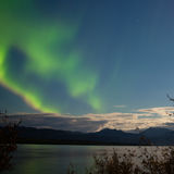 Aurora borealis moon-lit clouds over Lake Laberge Royalty Free Stock Images