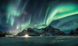 Aurora borealis of Noordelijke lichten over sneeuwberg op kustlijn stock afbeeldingen