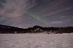 Aurora borealis, northern light over winter river landscape at night stock photography