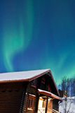 Aurora Borealis (Northern lights) above a cabin Royalty Free Stock Image