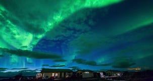 Aurora borealis (Northern Lights) above cabins stock footage