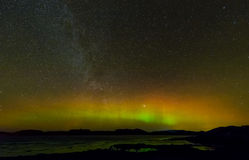 Aurora Borealis. The Aurora Borealis, or Northern Lights, low on the horizon, illuminating a clear sky over the central Norwegian coast. The Milky Way is visible Stock Photography