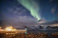 Aurora borealis op sneeuwberg met licht huis royalty-vrije stock fotografie