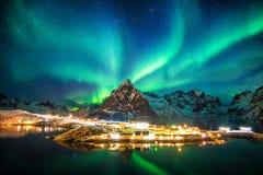 Aurora borealis over bergen in de visserij van dorp stock foto