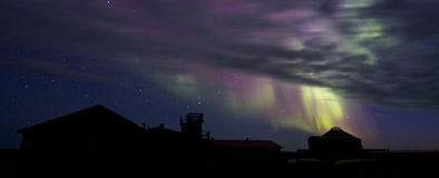 Aurora Borealis over a building silhouette Stock Photo