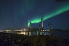 Aurora Borealis over city lights Stock Photo