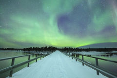 Aurora borealis over een brug in de winter, Fins Lapland stock afbeeldingen