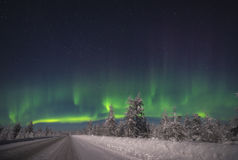 Aurora Borealis over the forest and road. Winter Landscape with aurora Borealis over the forest and road Stock Photo