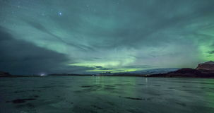 Aurora borealis over frozen lake stock video footage