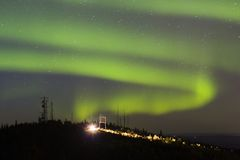 Aurora Borealis over hill with antennas and car with lights on royalty free stock images