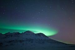 Aurora Borealis over a mountain. Aurora Borealis during winter in the arctic city of Tromso, Norway Royalty Free Stock Image