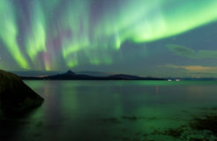 Aurora Borealis over Norwegian fjord. Vivid green lights in the sky at night caused by the Aurora Borealis seen over a Norwegian fjord due to ionized particles Stock Photos