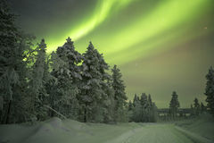 Aurora borealis over a track through winter landscape, Finnish L Stock Photos