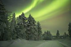 Aurora borealis over a track through winter landscape, Finnish L stock photos