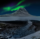 Aurora Borealis. Picture of aurora borealis or northern lights with the sky full of stars with the silhouette of Mt Kirkjufell in Snaefellsnes, Iceland stock image