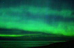 Night sky stars and aurora polar lights over sea Royalty Free Stock Images