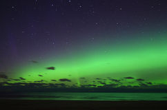 Aurora borealis polar lights and stars over sea Royalty Free Stock Images