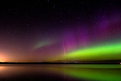 Aurora borealis with proton arc reflected over a lake Stock Photos