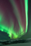 Aurora Borealis. Reds and greens and snow covered mountains stock photos