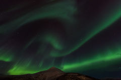 Aurora Borealis Scenery. Aurora Borealis across nightsky by a mountain Royalty Free Stock Photo