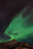 Aurora Borealis Scenery. Aurora Borealis with a funny shape almost connected to a mountain Royalty Free Stock Photography