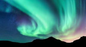 Aurora borealis and silhouette of mountains Royalty Free Stock Photos