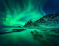 Aurora borealis, snowy mountain and sandy beach with stones. Aurora borealis above snowy mountain and sandy beach with stones. Northern lights in Lofoten islands royalty free stock photos
