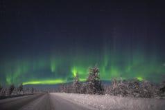Aurora Borealis sobre el bosque y el camino Foto de archivo