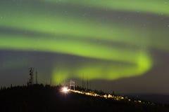 Aurora Borealis sobre la colina con las antenas y el coche con las luces encendido imágenes de archivo libres de regalías