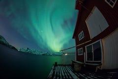 Aurora borealis sobre Tromso com casa de barco imagem de stock