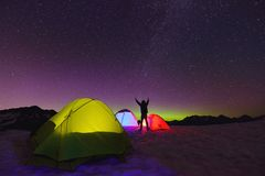 Aurora Borealis and tents on snow mountain Royalty Free Stock Photo