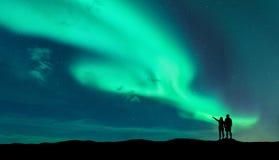 Aurora borealis und Schattenbild des Mannes und der Frau Stockfoto