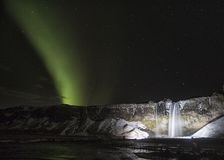 Aurora Borealis by waterfall in Iceland at night Royalty Free Stock Images