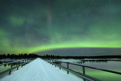 Aurora borealis in winter, Finnish Lapland. Spectacular aurora borealis (northern lights) over a bridge and a river in a snowy winter landscape in Finnish Royalty Free Stock Image