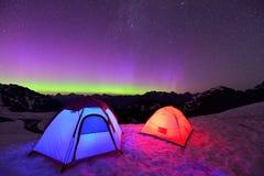 Aurora Borealis y tiendas en la montaña de la nieve Fotos de archivo libres de regalías