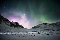 Aurora borealis z wschód słońca błyszczy nad pasmem górskim w obrazy stock