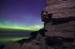 Aurora Curtains. Aurora Borealis photographed with cliffy seaside. Reflections on the water Royalty Free Stock Images