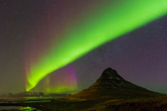 Aurora dancing with fully of stars on the sky. Over Kirkjufell volcano, Iceland winter season landscape Royalty Free Stock Photo