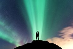 Aurora and hugging couple on the mountain peak Royalty Free Stock Photos