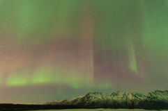 Aurora Over Mountains. Aurora lights up the sky and mountains Royalty Free Stock Images