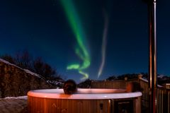 Aurora and night tub time. Enjoying a hot tub soak under a Magical northern lights in the arctic Norway stock photography