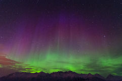 Aurora. The Northern green and purple Lights over mountains in Alaska Royalty Free Stock Photos