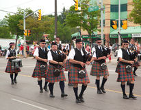 AURORA, ONTARIO, CANADA- JULY 1: Irishmen in their kilt playing their bagpipes during the Canada Day Parade. At part of Young Street in Aurora, Canada on July 1 stock image