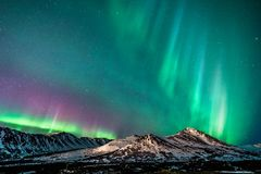 Colorful Aurora Over the Chugach Mountains. Northern lights over the moonlit Chugach Mountains in Anchorage, Alaska stock images