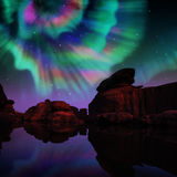 Aurora over lagoon. Multicolor aurora over lagoon and red rock Stock Photography